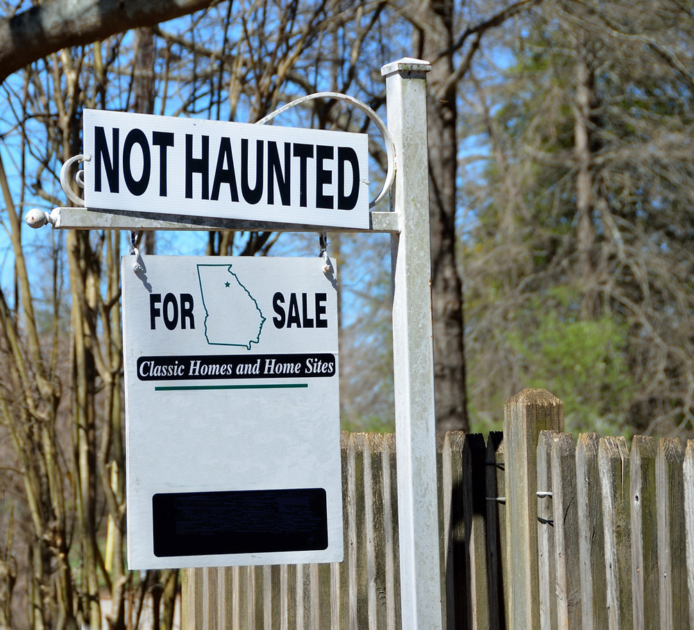"""An image of a for sale sign in front of a house. A large addition above the sign says """"NOT HAUNTED."""""""