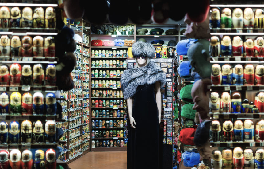 An image of the interior of a souvenir shop. A mannequin with a fluffly hat and coat stands in the midst of shelves packed with what appear to be Russian dolls.