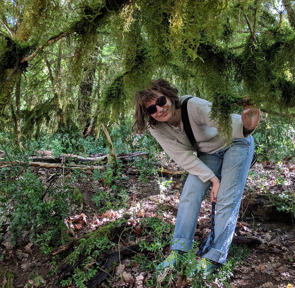 An image of Jane G. Six, a person in sunglasses crouching slightly to peek out from under a tree's branches.