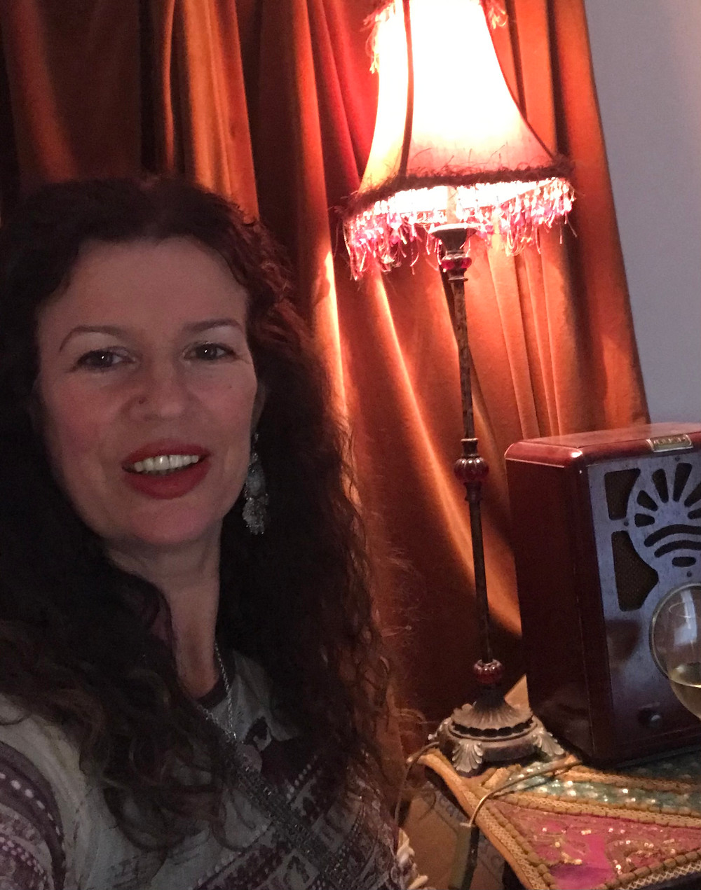An image of Kate Leimer, a person with long curly dark hair. She smiles into the camera. Alongside her is a lit lamp.