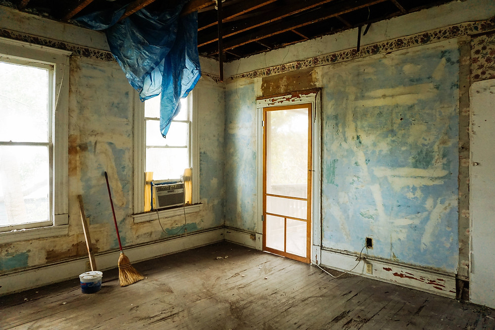 An image of the interior of what looks to be an abandoned home. A broom and bucket are set up on the floor, like someone was working here but has abandoned it.