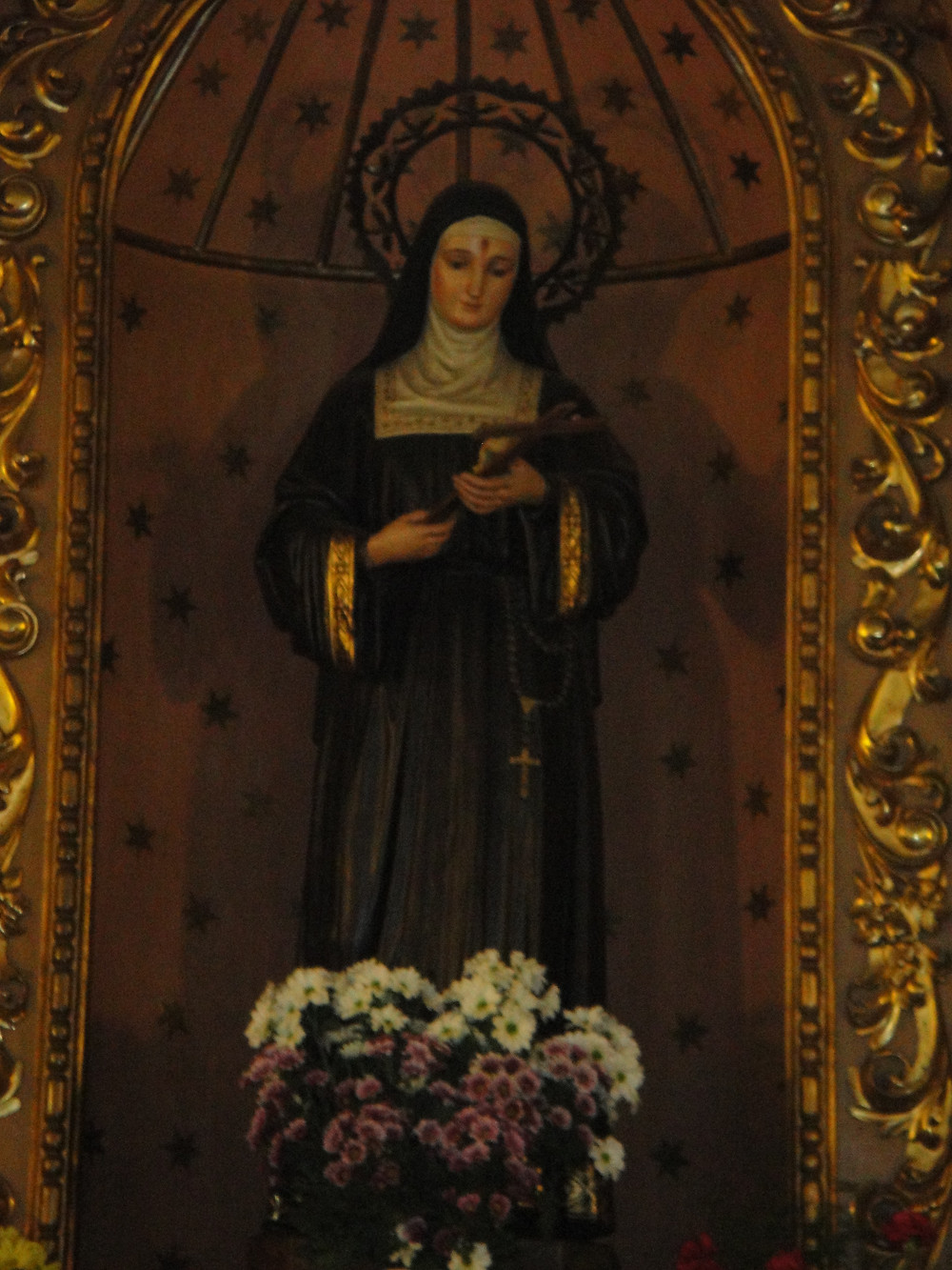 An image of a statue of St. Rita of Cascia, a woman in nun's robes. She holds a cross and her face is slightly downturned. There is a spot of blood on her forehead. A large bouquet of flowers is placed at her feet.