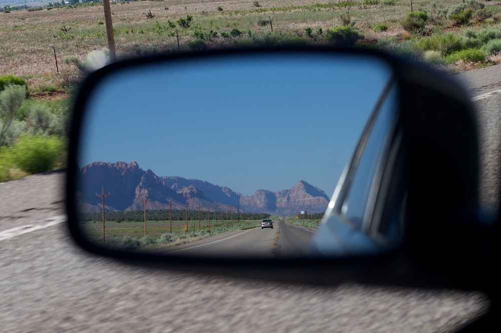 An image of a road, taken from the rearview mirror of a car. The blue sky and mountains can be seen.