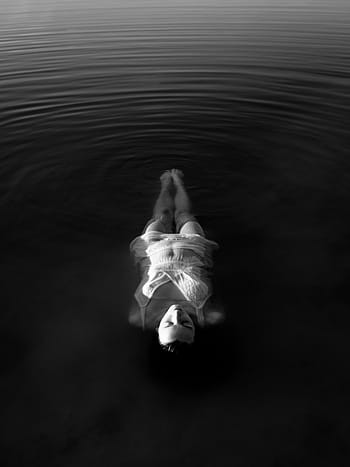 A grayscale image of a person floating in the water with their eyes closed.