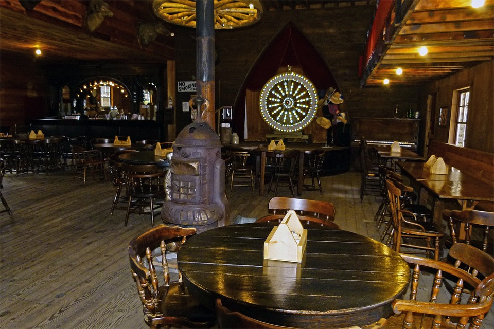 An image of the interior of a vintage saloon. Tables and a bar are visible, and a lit-up wheel on the wall.