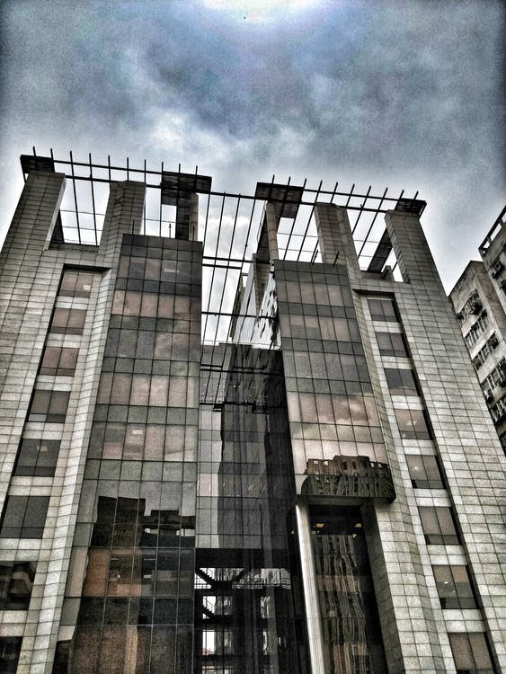 An image of a derelict building against a cloudy gray sky. The iron structure of the building is exposed, and it is visibly degrading,