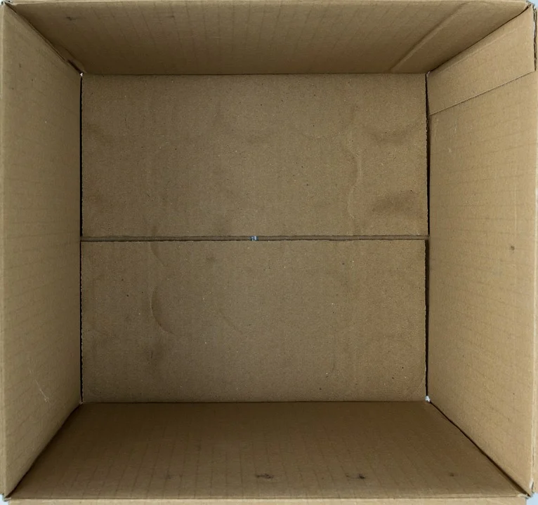 An image of the interior of a cardboard box, slightly indented and dirty from use.