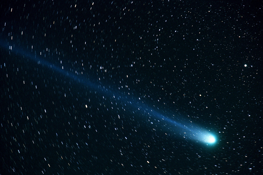 An image of a comet streaking across a starry sky.