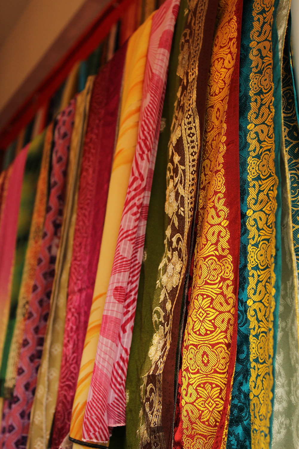 A collection of brightly-colored fabrics overlaid over one another. They are covered in intricate golden detailing.