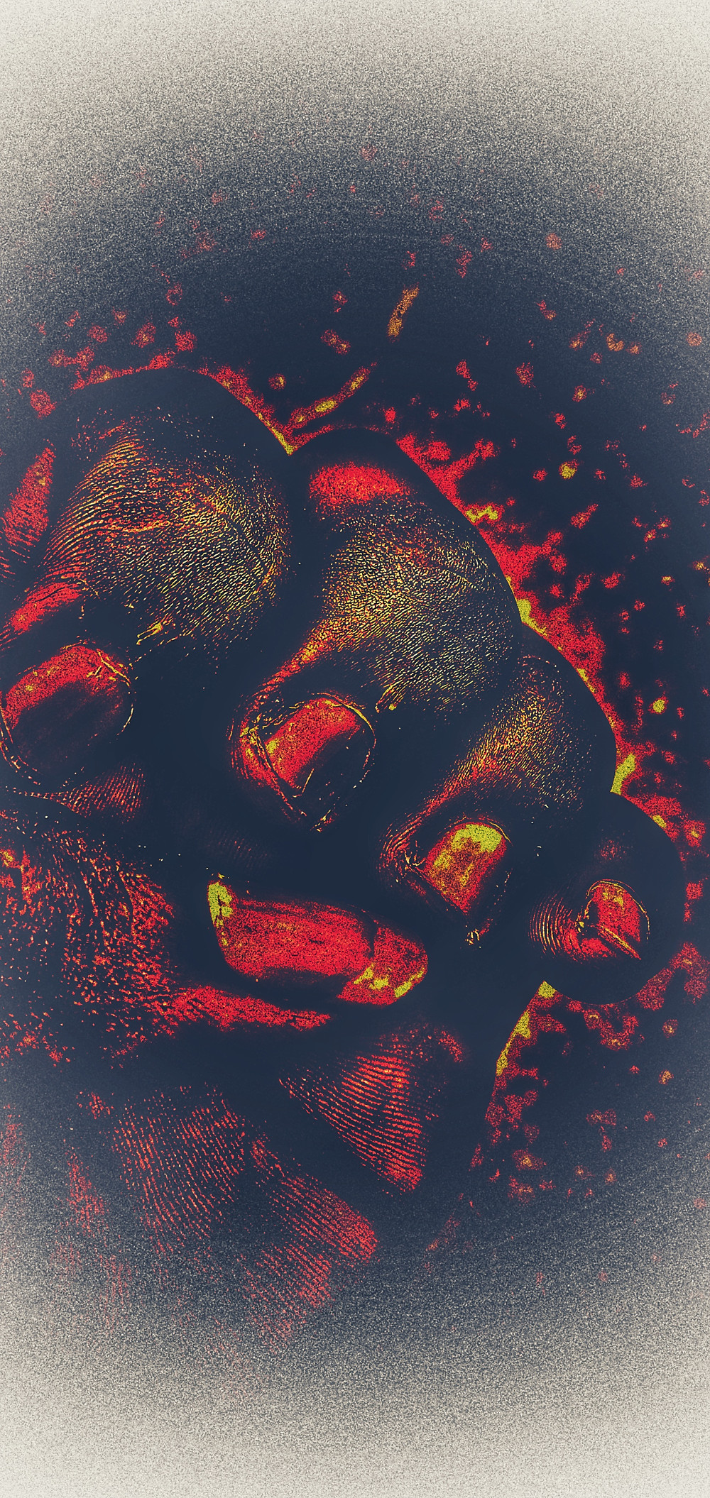 An edited image of a dark-skinned hand clenched in a fist. A red and orange filter is placed upon it, making the area around the fist appear wreathed in color.