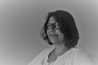 A grayscale image of Pam Knapp, a person with shoulder-length dark hair and glasses smiling from a three-fourths angle.