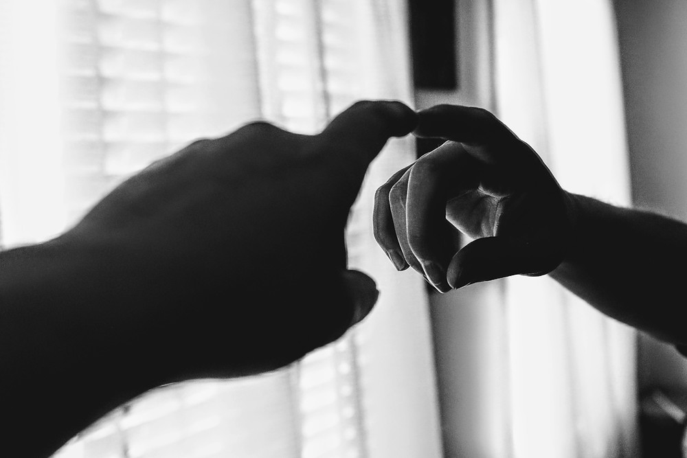 A black-and-white image of a dark hand reaching out towards a mirror, with one finger touching its surface. The hand is perfectly reflected in the mirror, creating the illusion of two fingers touching.