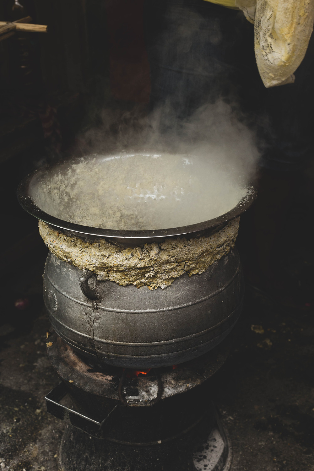 An image of a steaming cauldron, with mud caked around its edge.