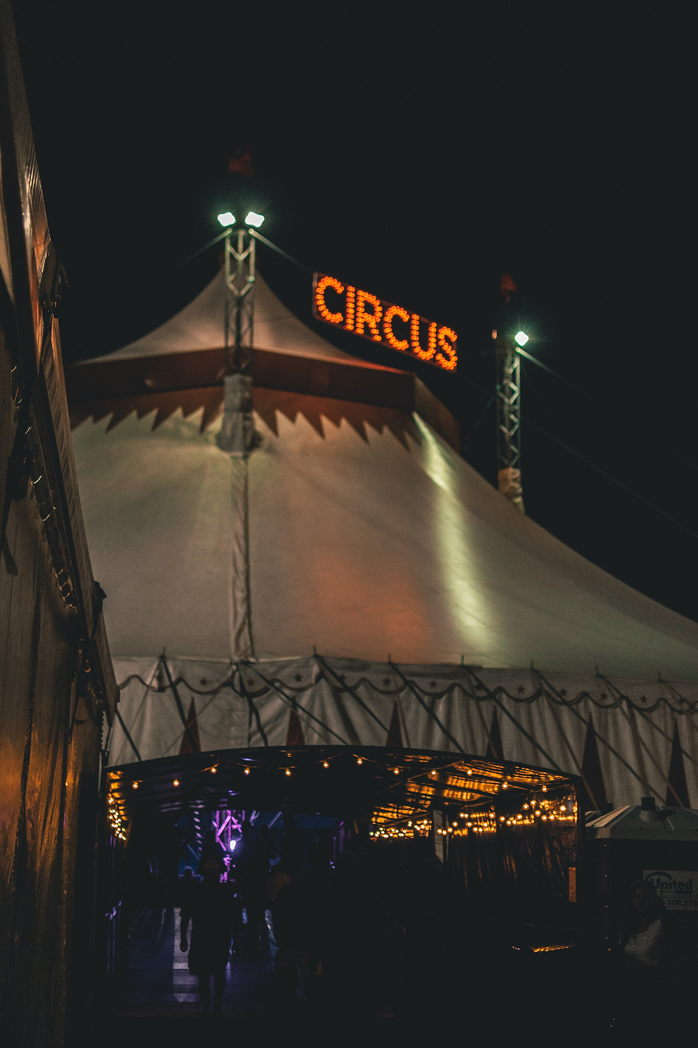 "An image of a circus tent at night, illuminated by a large sign that says ""CIRCUS."""