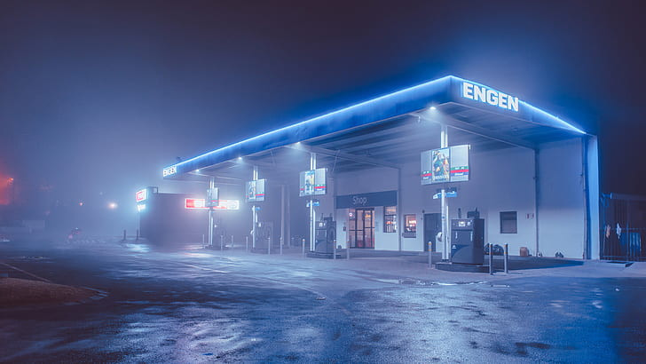 An image of a truck stop at night, illuminated in bright blue neon.