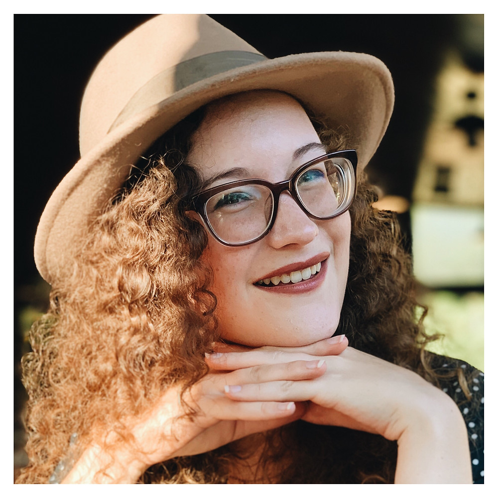 An image of Tara Fritz, a person in a hat and glasses. They rest their chin on their hands and smile at the camera.