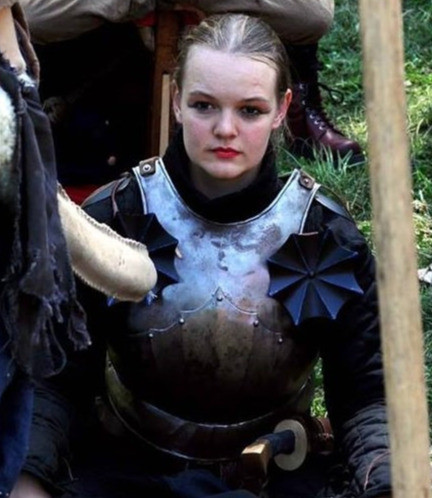 An image of Alexandra Haverská, a person wearing a suit of armor. Their face is uncovered and their hair is pulled back. They look slightly to the side of the camera.