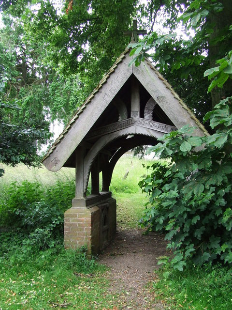 An image of a lych gate, a gateway covered with a roof found at the entrance to a traditional English or English-style churchyard. This gate is half-covered with the surrounding plant life, with a gently-trodden path winding through it.