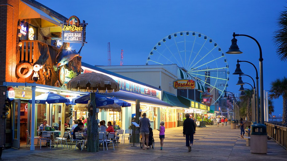 An image of a boardwalk in early evening. Several storefronts light up the walk, and a ferris wheel can be seen in the background. A few small groups of people stroll along, whilst some eat in front of a storefront for a bar & grill.