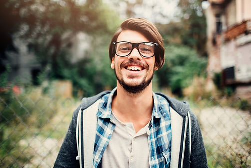 Smiling man with brown hair and glasses.