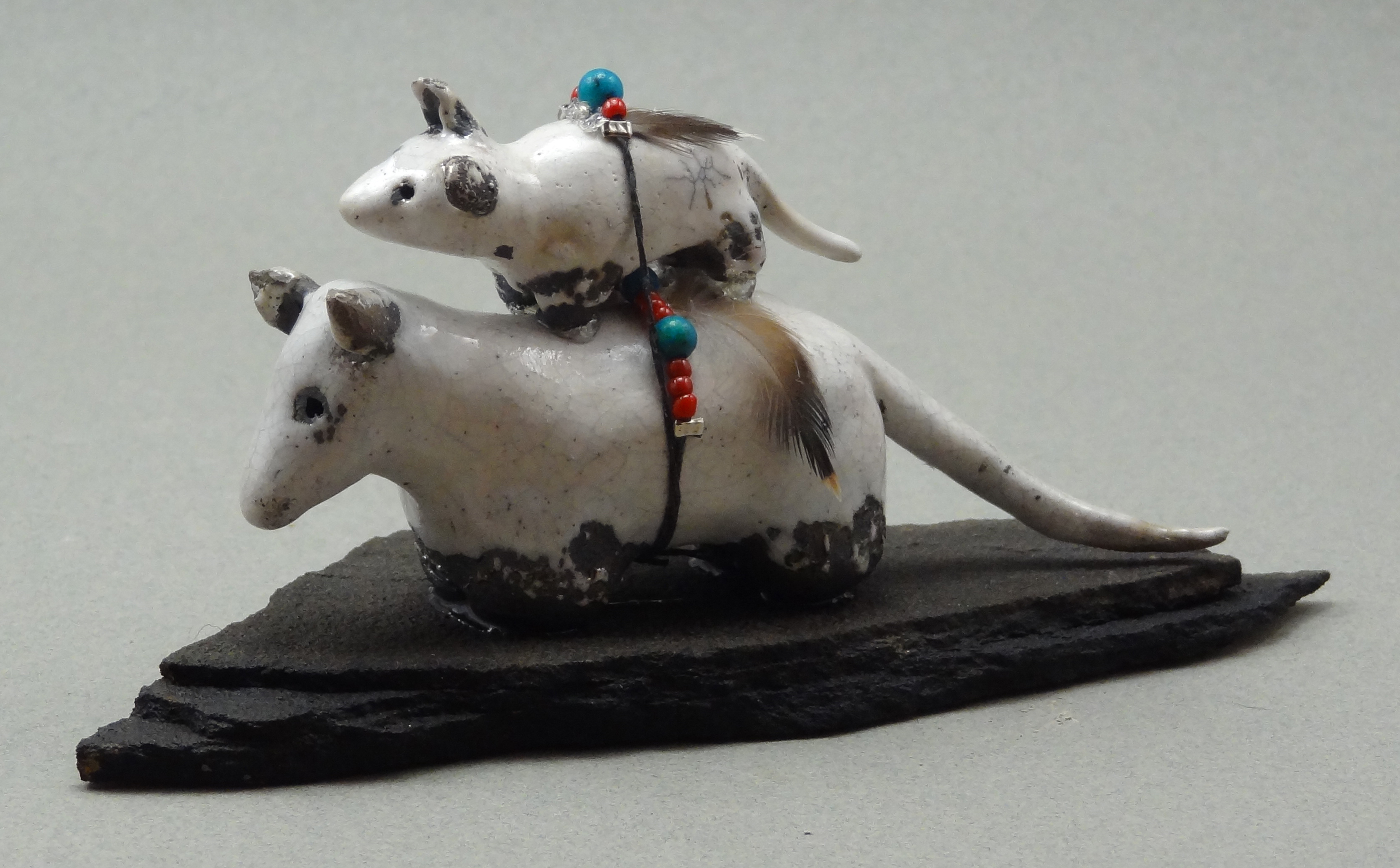 Possum and baby, White Crackle glaze, raku fired, 4 x 2 x 1 inch, mounted on flagstone