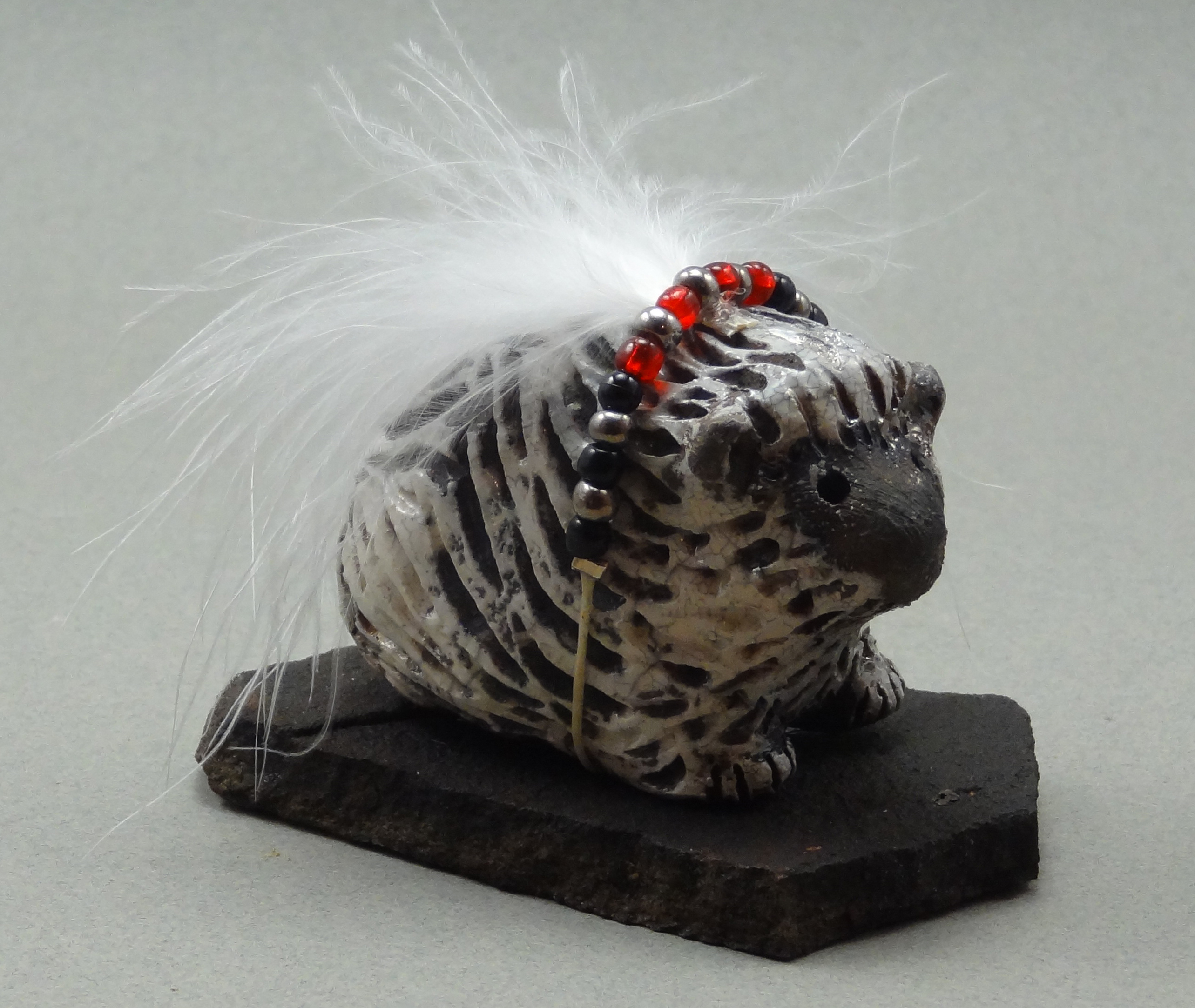 Porcupine, White Crackle glaze, raku fired, .5 x 1.5 x .5 inches, mounted on flagstone