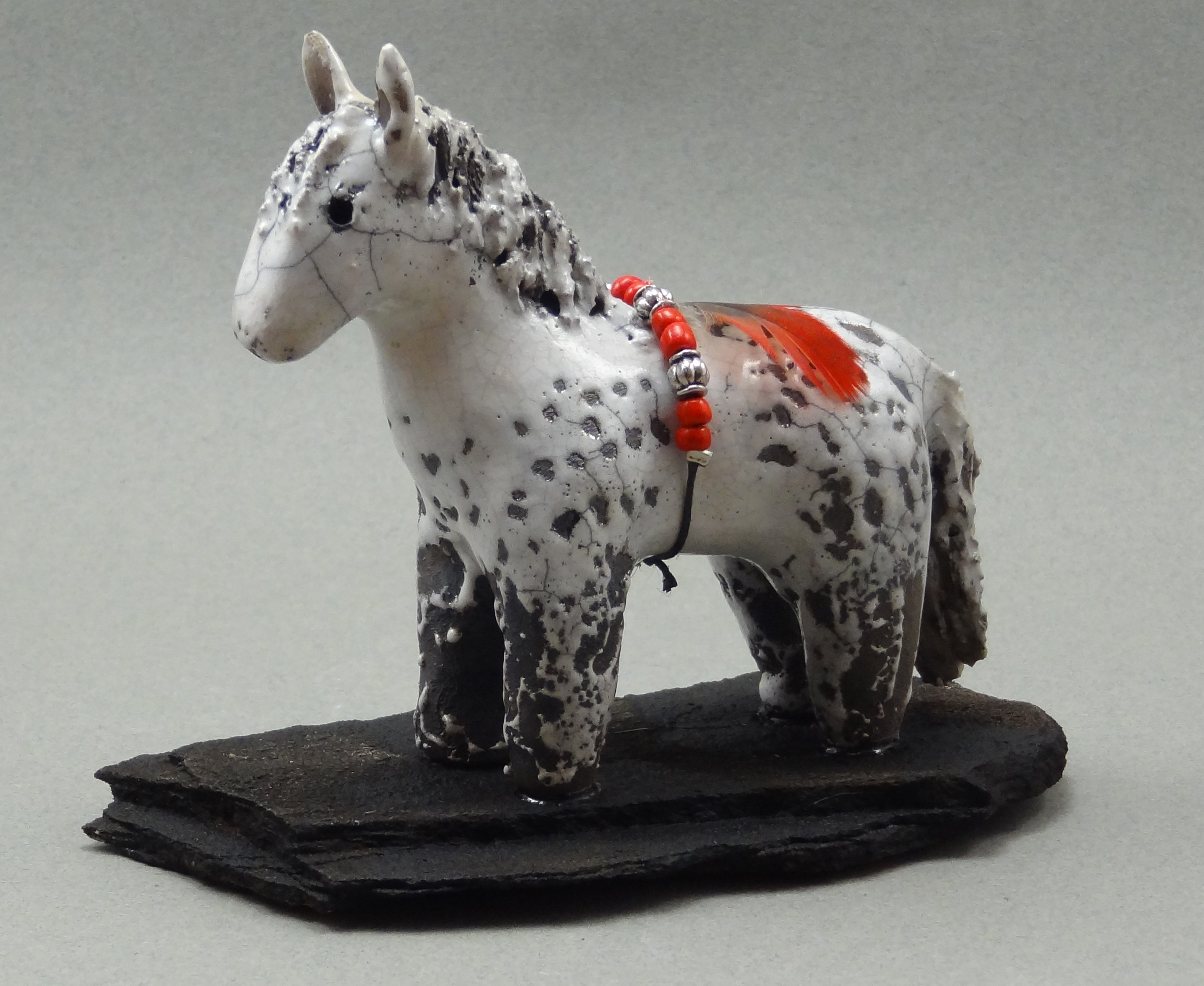 Horse, White Crackle glaze, raku fired, 4 x 3.5 x 1 inch, mounted on flagstone