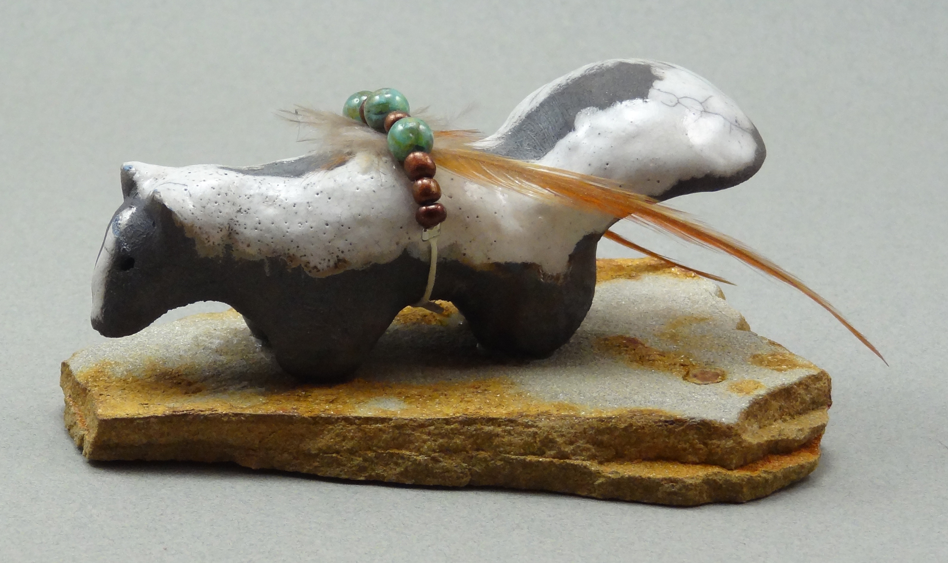 Skunk, White Crackle glaze, raku fired, 4 x 1 x 1.5 inches, mounted on flagstone
