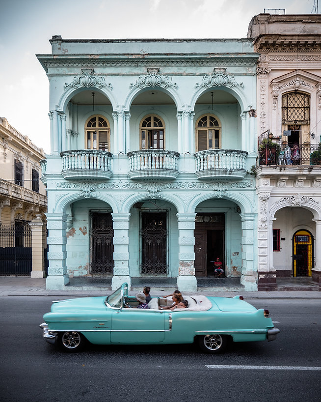 a cyan convertible vintage car with tourists in Havana/Cuba in front of a cyan painted house