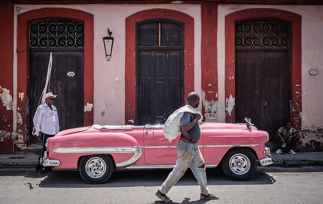 a man is crossing in front of a vintage car