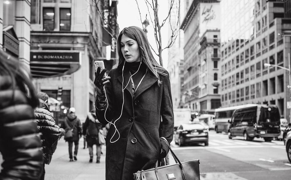 Ein Frau läuft durch die Straßen von New York City. Sie schaut auf ihr Smartphone, das mit einem Headset verbunden ist.