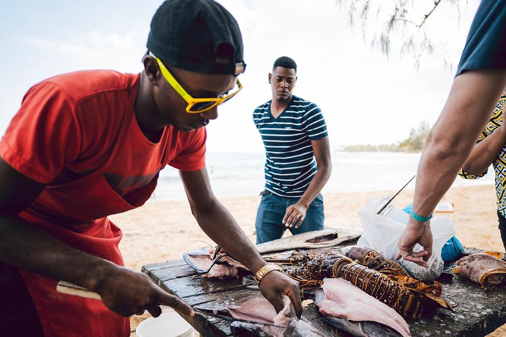 Las Terrenas: Am späten Vormittag legen hier die Fischerboote an. Die jungen Fischer zerlegen den frischen Fisch an Ort und Stelle. Am Strand sind auch Einheimische, die sich an einfachen Grillbuden versorgen.