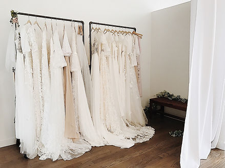 Rack of Flora and Lane boho wedding dresses in their Chicago bridal shop.