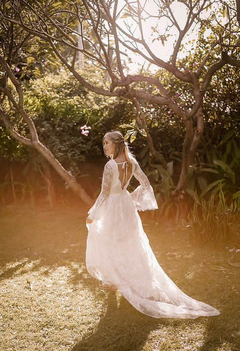 A bride taking a stroll in a garden while wearing the Primrose wedding gown by Flora and Lane.