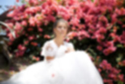 Bride sitting down in her bohemian wedding dress in front of bougainvilleas.