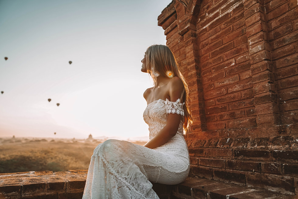 Bride wearing the Moonlight wedding dress by Flora and Lane while peering out towards hot air balloons in the distance as she sits atop a ancient temple wall.