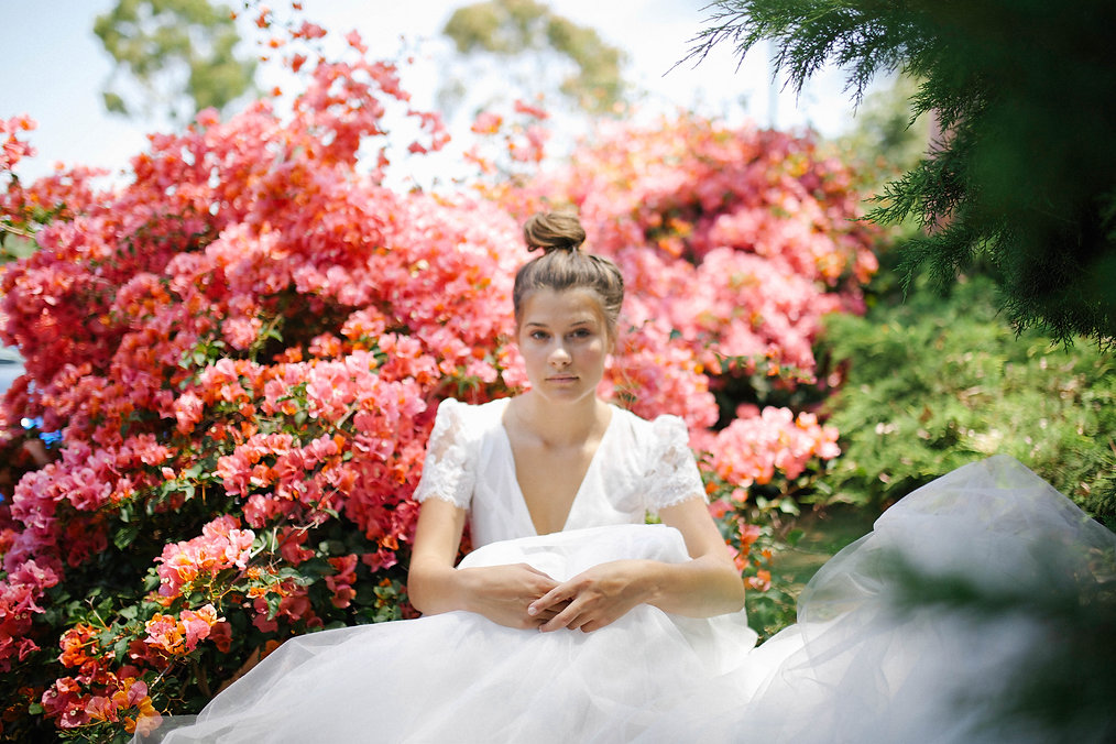 Bride staring into camera while sitting in front of bougainvilleas.