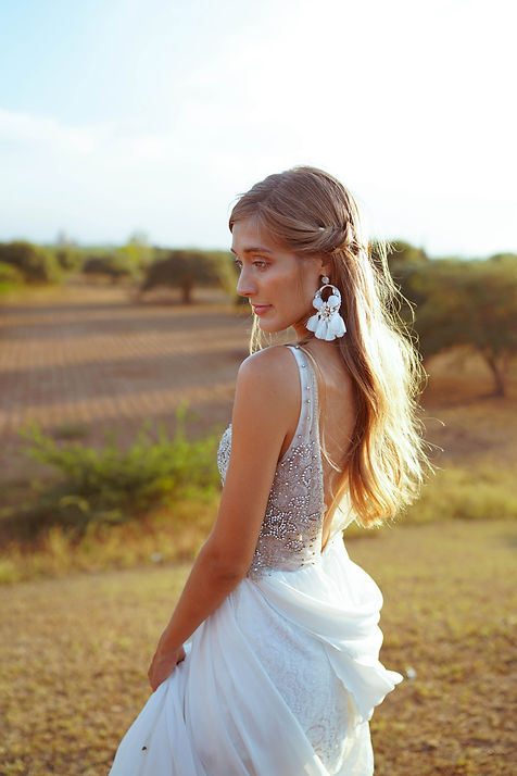 Side view of bride in Laguna gown from Flora and Lane with bohemian earrings.