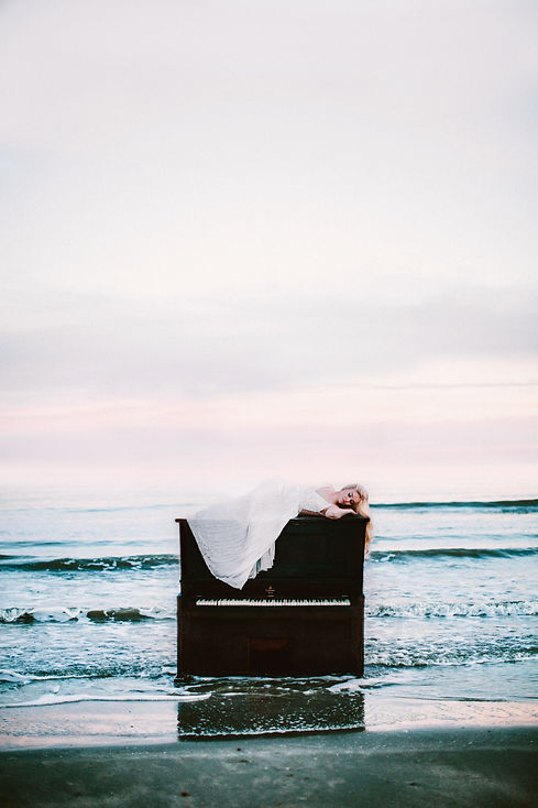 Bohemian bride laying atop a dresser that is placed artistically in front of a shoreline.