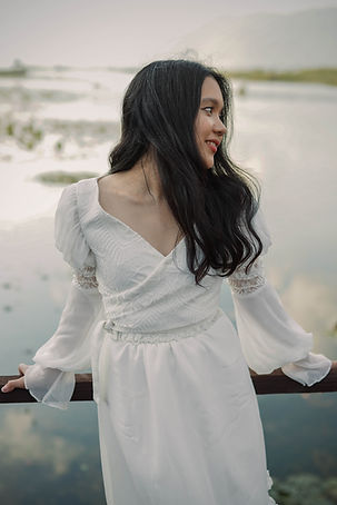 Catherine Yatana, the founder of Flora & Lane in a wedding dress posing next to a beautiful lake.