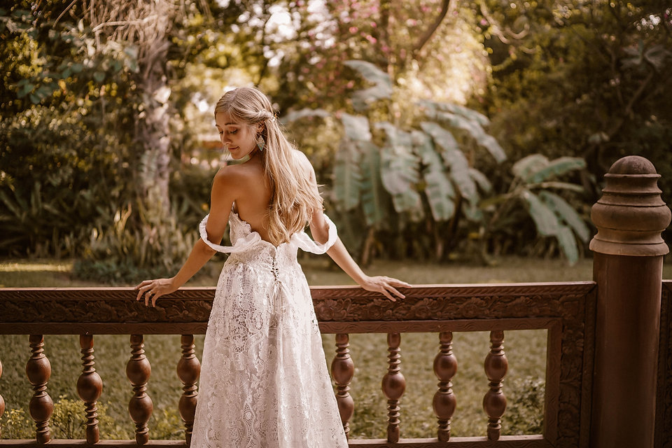 A bride peering over her shoulder softly while wearing the Indie wedding gown from Flora and Lane.