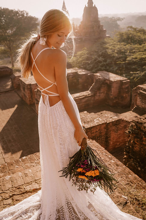 Bride in Flora and Lane's Giselle gown holding a bouquet on top of an ancient wall.
