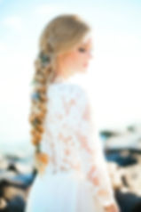 Bride with hair braided beautifully with flowers in a Flora & Lane bohemian wedding dress.