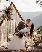 Boho bride dipped by groom in front of mountain backdrop.