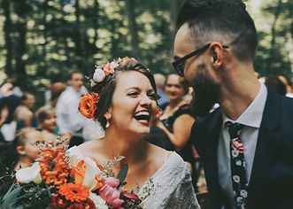 Bride with bohemian flower crown smiling at her groom.
