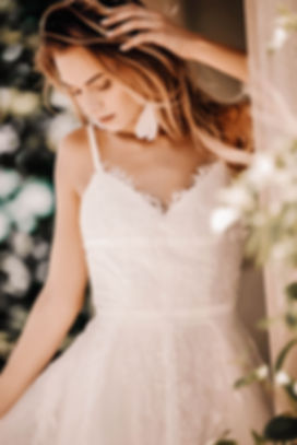 Bride wearing the Gilian gownby Flora and Lane with eye catching white feather earrings.