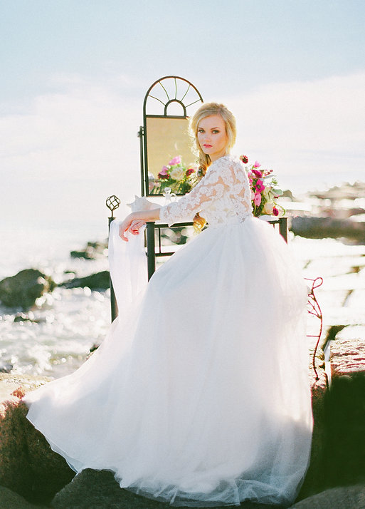 Boho bride sitting in front of a vanity that has been set up by the ocean.
