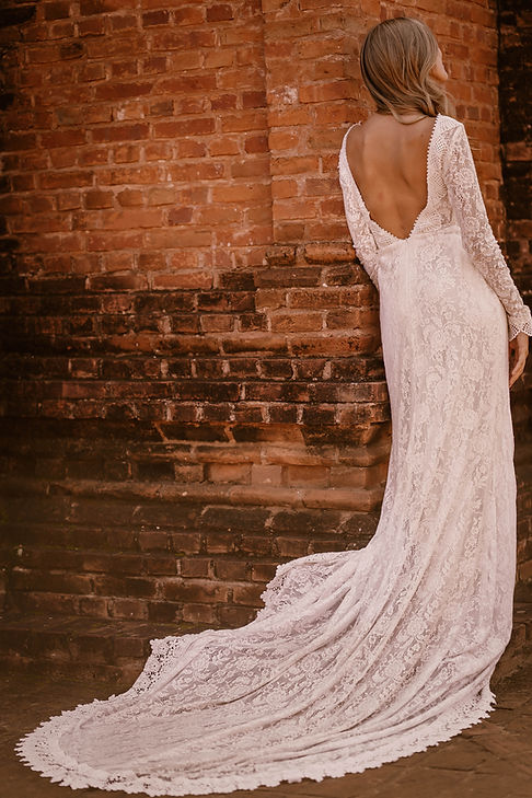 Bride wearing the Venice gown by Flora and Lane while leaning against an red brick wall.