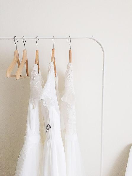 Close up shot of rack with Flora & Lane 's boho wedding dresses.