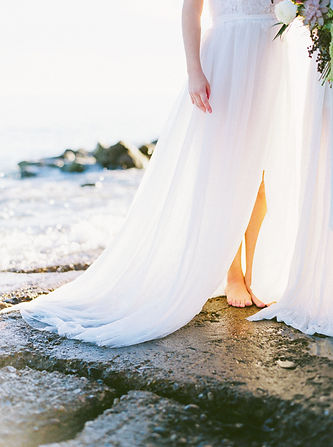 Skirt of a barefoot bohemian bride posing by the sea.